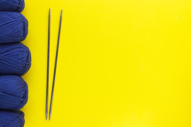Breigarens van klassieke blauwe denimkleur en metalen naalden op gele achtergrond. ballen van wol draden. handgemaakt en hobbyconcept. platliggend, bovenaanzicht met kopieerruimte. Premium Foto