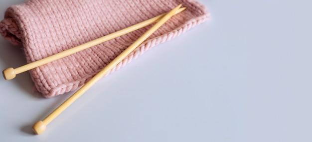 Breinaalden en roze garen op de witte achtergrond