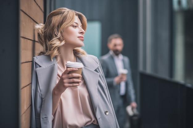 Breken. mooie jonge blonde vrouw in bedrijfsjasje die zich nadenkend met koffie bevinden die tegen muur van bureaugebouw en man leunen