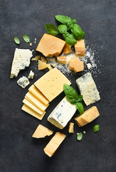 Brie, blauwe kaas, parmezaan en basilicum op een zwarte betonnen tafel.
