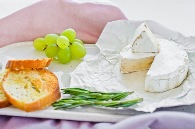 Brie-kaas met noten op een witte scherpe raad