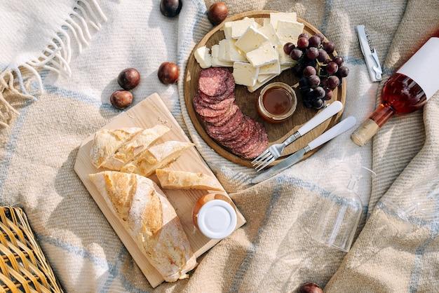 Brie-kaas met salami, druiven en honing op een houten bord. vers stokbrood. eten en drinken concept.