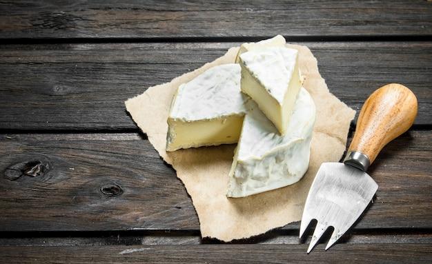 Brie-kaas op oud papier. op een houten achtergrond.