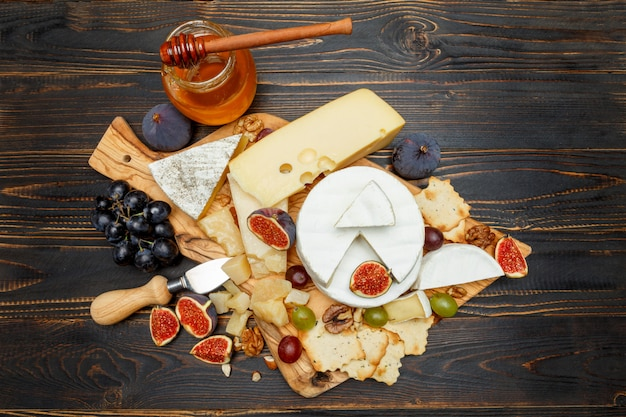 Brie op een houten bord met verse vijgen en druiven