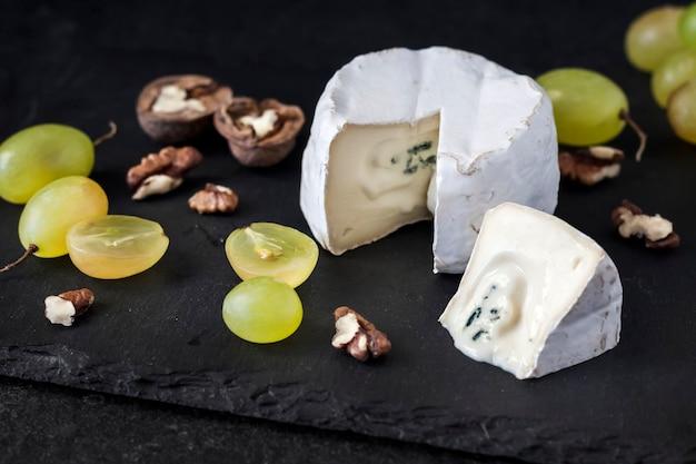 Brie soort kaas. zachte kaas met druiven en walnoten op zwarte achtergrond
