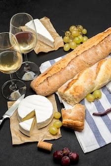 Brie, stokbrood en twee glazen witte wijn op donkere concrete achtergrond