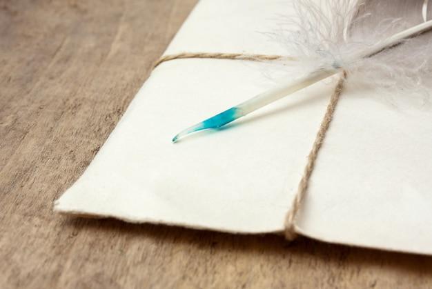 Brief en een ganzenveer op een houten tafel
