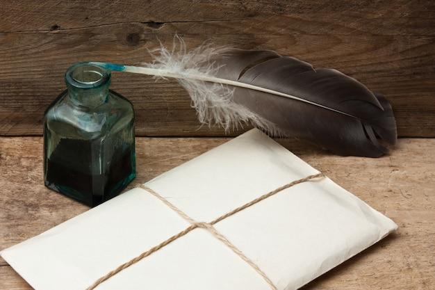 Brief en ganzenveer met inkt op een houten tafel