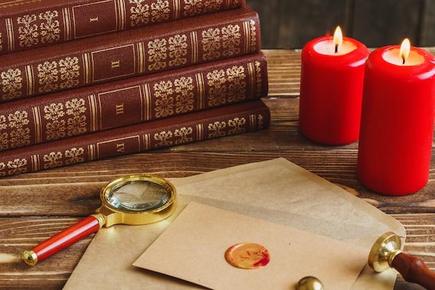 Brief met grondzegel, vergrootglas en brandende kaarsen op houten tafel