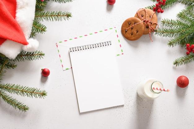 Brief voor de kerstman, zelfgemaakte peperkoekkoekjes en melk op wit.