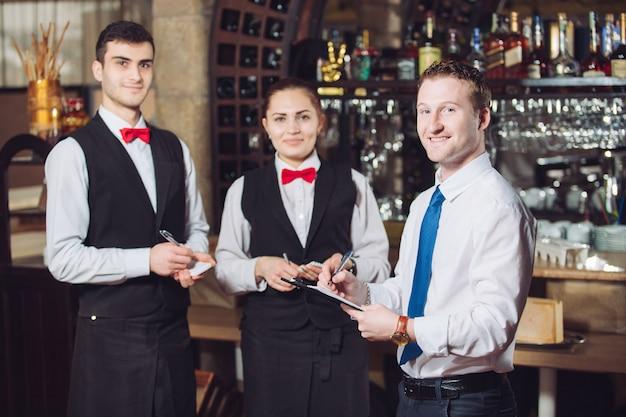 Briefing van de manager met de obers. restaurantmanager en zijn personeel.