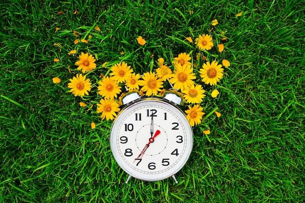 Briefkaart goedemorgen en wekker met gele bloemen liggen op het groene gras