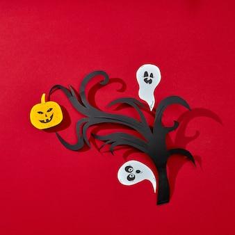 Briefkaart voor halloween-handwerk van papieren geesten en pompoenen met enge gezichten op een tak gepresenteerd op een rode achtergrond met weerspiegeling van schaduwen en ruimte voor tekst. plat leggen