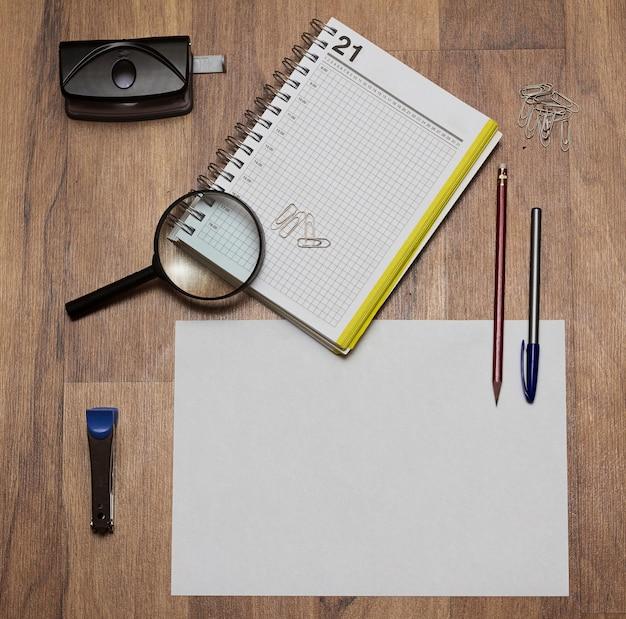Briefpapier bestaande uit een notitieboekje, een lus, een nietmachine en een perforator op de tafel