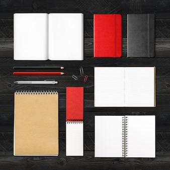 Briefpapier, boeken en notebooks mockup sjabloon geïsoleerd op zwarte houten achtergrond