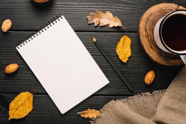 Briefpapier en bladeren in de buurt van thee en doek