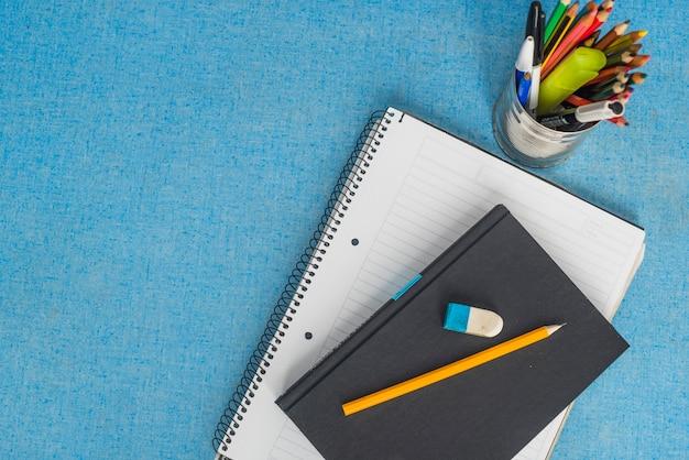 Briefpapier en leerboek op blauw
