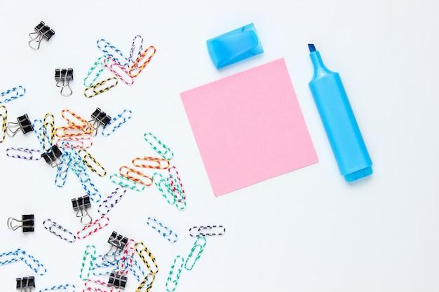 Briefpapier kantoorbenodigdheden. paperclip, viltstift, memo stuk papier op witte achtergrond