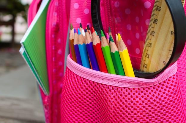 Briefpapier objecten. schoolspullen zitten in schoolrugzak. afgezwakt beeld.