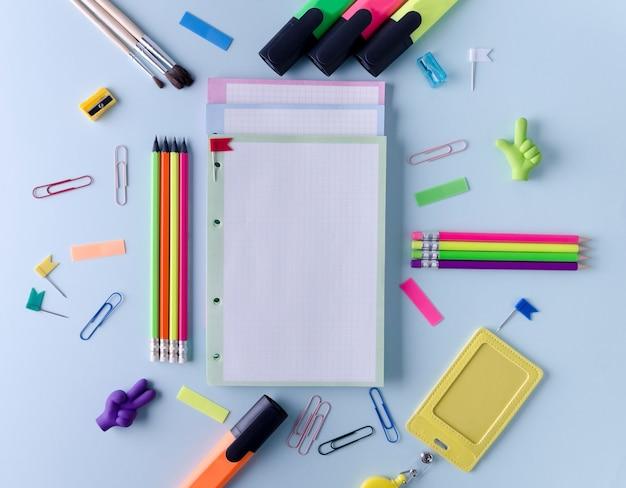 Briefpapier voor school en kantoor, notitieblok, kleurpotloden, stiften liggen op een blauwe achtergrond.