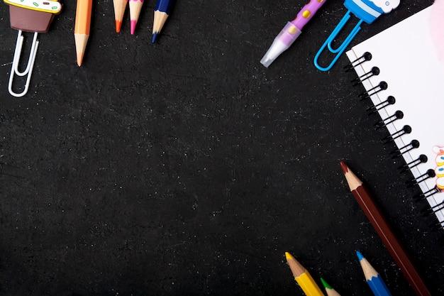 Briefpapier vormde een kader op een zwarte achtergrond. terug naar schoolconcept met exemplaarruimte