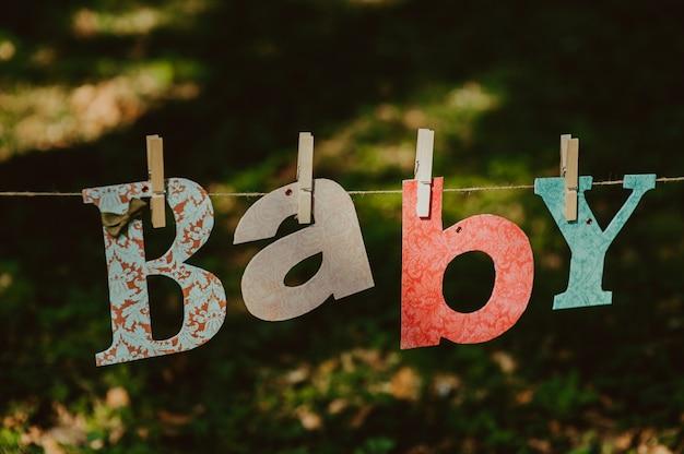 Brieven van woord baby en gebreide sokken opknoping op kledinglijn