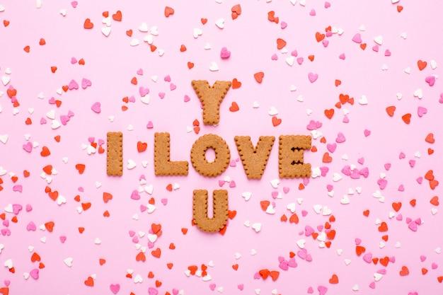 Brievenkoekjes i love you met roze en rode harten op roze