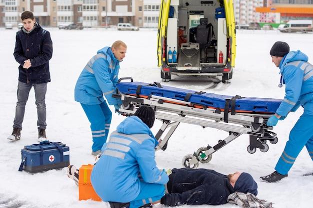 Brigade van jonge paramedici in werkkleding brancard voorbereiden op zieke onbewuste man liggend in de sneeuw
