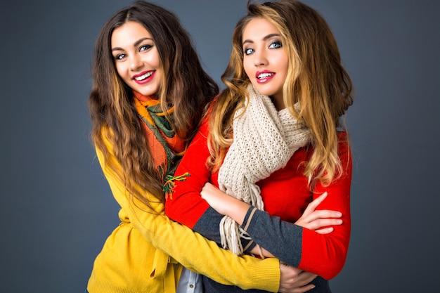 Bright fashion herfst winter portret van twee mooie blonde en brunette vrouw, felle kleur matten stijlvolle truien en sjaals dragen