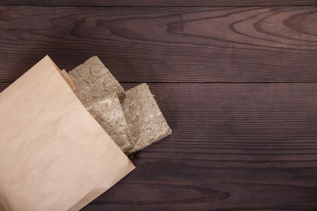 Briketten van zonnebloemhalva liggen in een papieren zak op een houten ondergrond. geen afvalconcept.