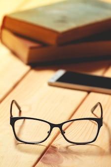 Bril, boeken en mobiele telefoon op een houten tafel