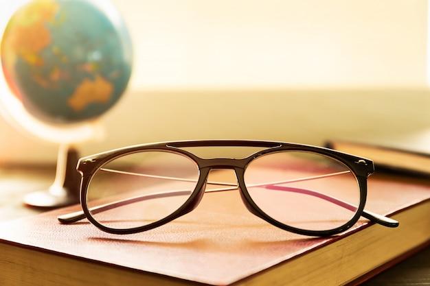 Bril en boeken naast het raam