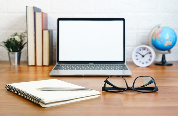 Bril en notitieblok met laptop op dek werkplek met laptop op tafel thuis at