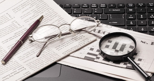 Bril en oude krant liggend op de zwarte opengeklapte laptop