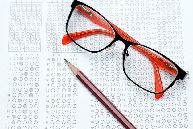 Bril en potlood op gestandaardiseerd testformulier met antwoorden gebubbeld en een potlood, focus op antwoord s