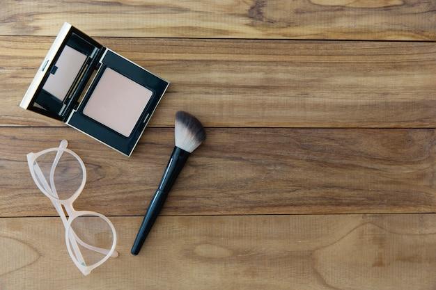 Bril in de buurt van compact poeder en borstel