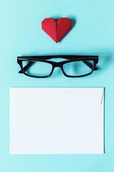 Bril in donker montuur, witte lege envelop en rood hart van origami