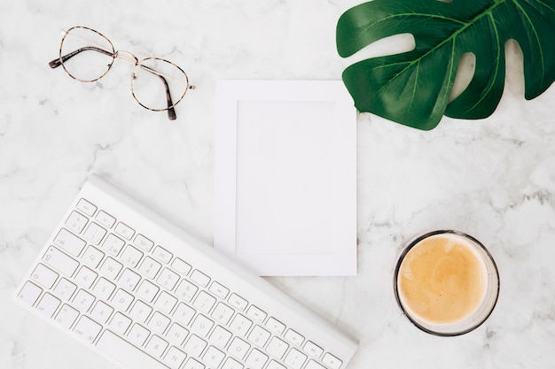 Bril; koffie glas; monster blad en fotolijst met toetsenbord op witte marmeren gestructureerde achtergrond