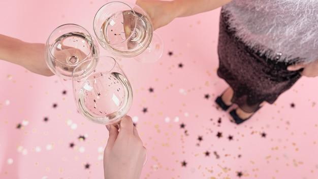 Bril met champagne in de handen van meisjes op een feestje op een roze achtergrond, kopieer ruimte.