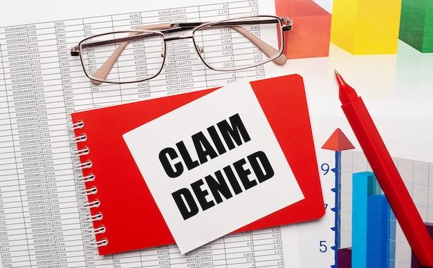 Bril met gouden rand, een rode pen, kleurentabellen en een rood notitieboekje met een witte kaart met de tekst claim denied