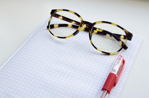 Bril met hoornen montuur, pen met rode inkt op een geruit notitieboekje. het concept van leren, studentenlichaam, lesgeven