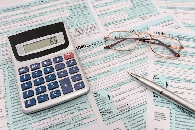 Bril met rekenmachine en pen op formulier 1040