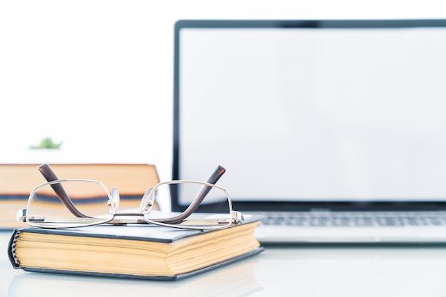 Bril op boek met leeg scherm laptopcomputer aan dek, werkplek met laptop en boek op tafel thuis, werkformulier thuisconcept