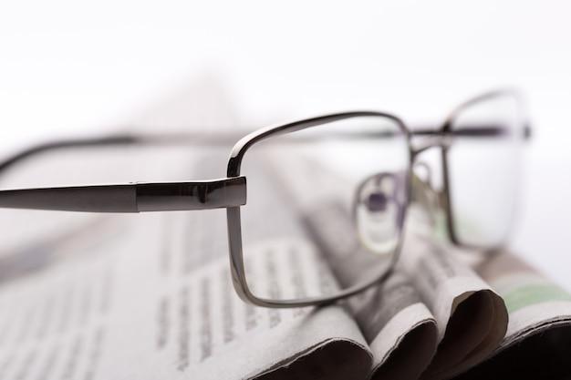 Bril op de krantenclose-up