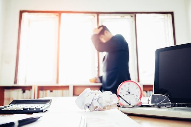 Bril op laptop toetsenbord en kantoor apparatuur op bureau met wazige achtergrond van zakenman werken tot koffie pauze met stress concept