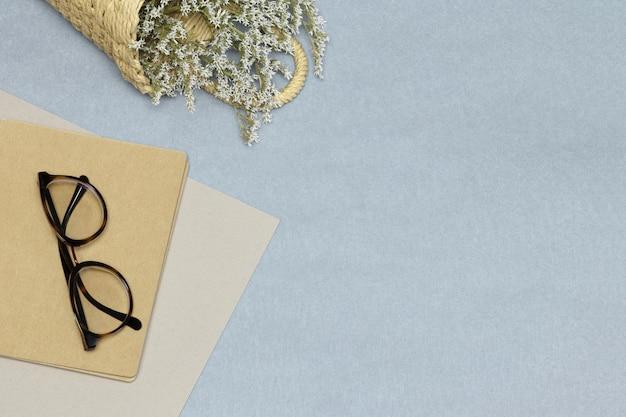 Bril op notitieboekje, roze documenten en stromand met bloemen