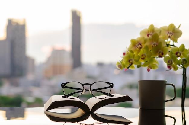 Bril op open boek gezet met kopje koffie phalaenopsis orchidee en city