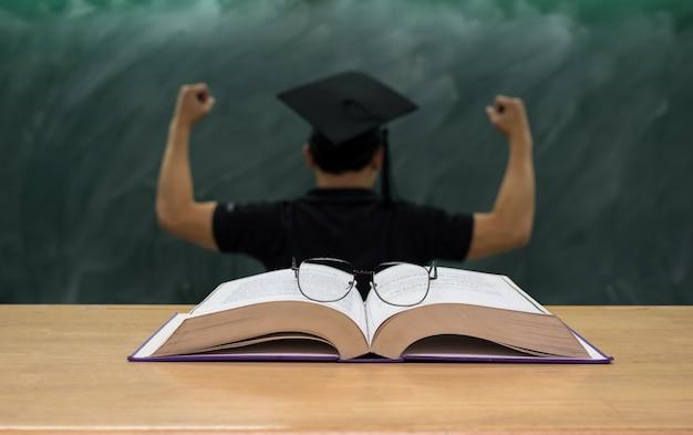 Bril over de boeken op het bureau in de klas met de man