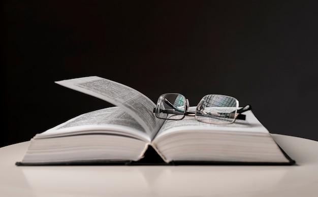 Bril over open boek. onderwijsconcept met exemplaarruimte.