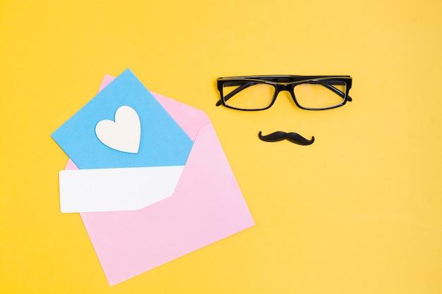 Bril, snor, roze envelop, houten hart en een kaart op een gele achtergrond, vaderdagconcept